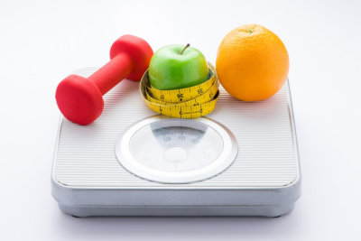 Dieting weight-loss slim down concept. Closeup measuring tape on white weight scale